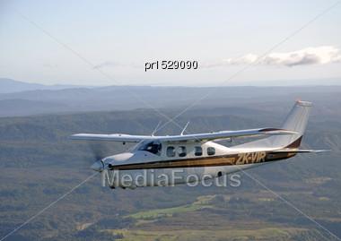 Cessna 210 Light Aircraft Flying Over Westland, New Zealand Stock Photo
