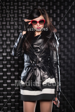 Charming Brunette Wearing Black Jacket And Red Sunglasses Posing With A Mobile Phone Stock Photo