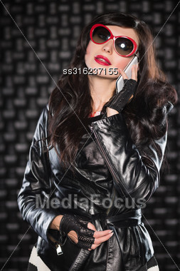 Charming Lady In Black Leather Jacket And Red Sunglasses Talking On The Phone Stock Photo