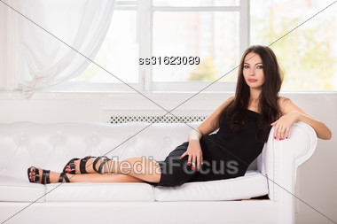 Charming Young Brunette In Black Dress Posing On The White Sofa Stock Photo