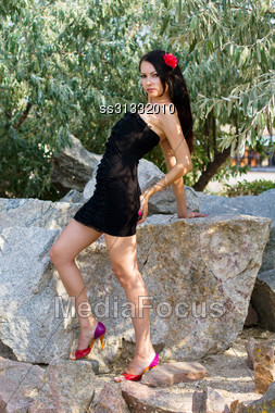 Charming Young Woman In Black Dress Outdoors Stock Photo