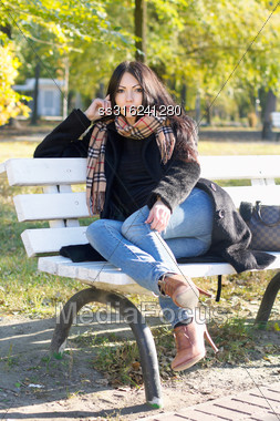 Charming Young Woman Sitting On A Bench In Autumn Park Stock Photo