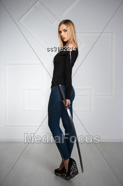 Charming Young Woman Wearing Blue Jeans And Black Blouse Posing With Sword Stock Photo