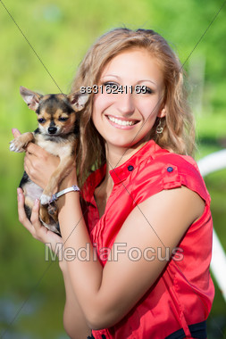 Cheerful Blond Woman Posing With A Small Dog Stock Photo