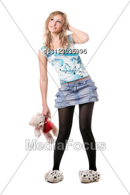 Cheerful Blonde In Slippers Posing With Teddy Bear Toy. Stock Photo