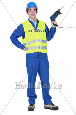 Cheerful Builder Holding Drill Stock Photo
