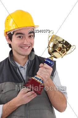 Cheerful Laborer With Gold Cup Stock Photo