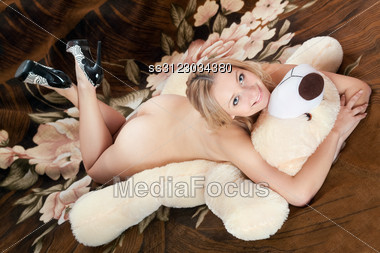 Cheerful Naked Young Blonde Lying On A Large Teddy Bear Stock Photo