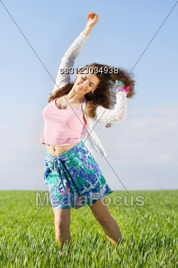 Cheerful Nice Young Woman In A Green Field Stock Photo