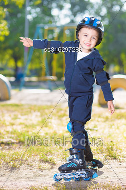 Cheerful Skater Boy In Helmet Rollerblading Near The Playground Stock Photo