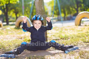 Cheerful Skater Boy In Helmet Sitting Under The Tree Stock Photo