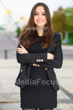 Cheerful Woman In Black Clothes Posing Outdoors Stock Photo