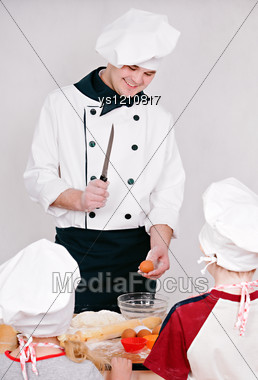 Chef Is Teaching Kids To Cook On The Grey Background Stock Photo