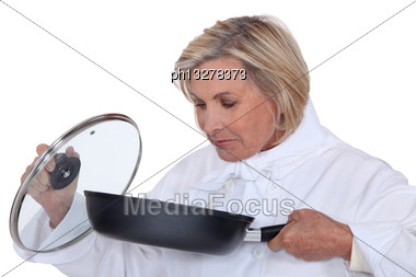 Chef Smelling A Saucepan Stock Photo