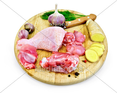 Chicken Leg Cut On A Round Board With Garlic, Parsley, Ginger And A Knife Isolated On White Background Stock Photo
