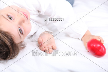 Child Holding A Plastic Heart Stock Photo