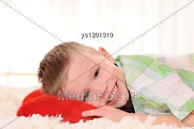 Child Is Lie On The Floor With A Red Plush Heart Stock Photo