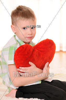 Child Sit On The Floor With A Red Plush Heart Stock Photo