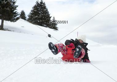 Child sledding on Plastic Sled Stock Photo