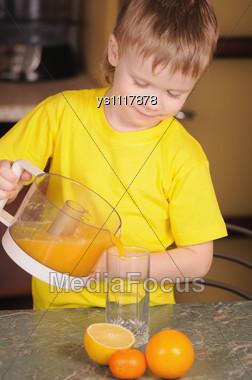 Child In A Yellow Vest Drinks Orange Juice Stock Photo