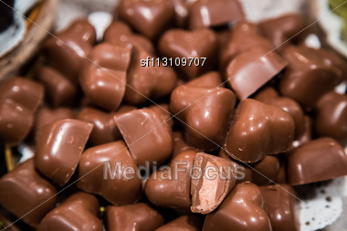 Chocolate Candies Of Different Shapes And Broken Pieces Of Chocolate. Delicious Food Background. Selective Focus On The Candies Stock Photo