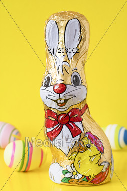 Chocolate Easter Bunny And Eggs, Isolated Over Yellow Stock Photo