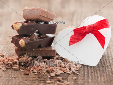 Chocolate Pieces On Wooden Background With Heart Symbol Stock Photo
