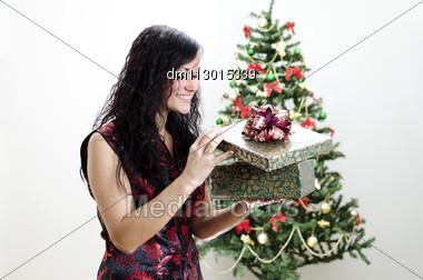 Christmas: Brunette Girl With Gift Stock Photo