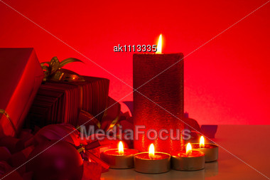 Christmas Gifts And Candles Over Red Background Stock Photo