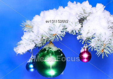 Christmas And New Year Decoration- Balls With Real Snow-covered Fir Branches .On Blue Background Stock Photo