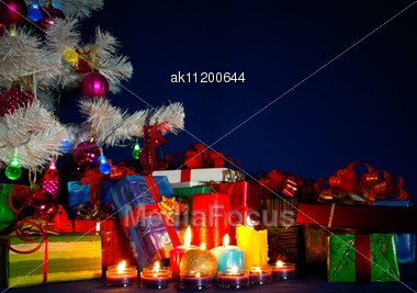 Christmas Presents And Burning Candles Against Blue Background Stock Photo