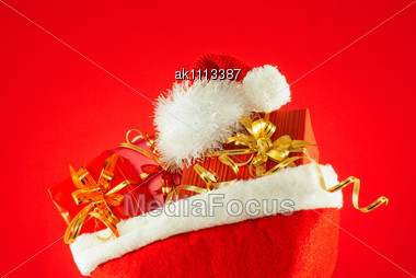 Christmas Presents With Santa's Hat Against Red Background Stock Photo