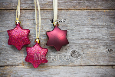 Christmas Star Baubles Hanging On The Wooden Background Stock Photo