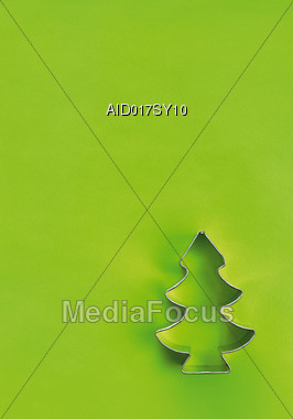 Christmas Tree Cookie-Cutter Over Green Backgrpound Stock Photo