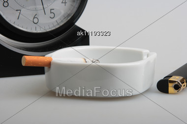 Clock And White Ashtray With Cigarette. Studio Photography. Close-up Stock Photo