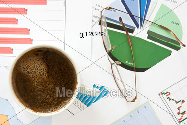 Close- Up Of Coffee Cup, Glasses And Business Charts Stock Photo
