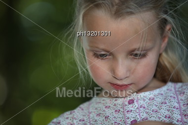 Close Shot Of Fair-haired Schoolgirl With Downcast Eyes Stock Photo