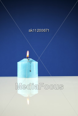 Close Up Of Burning Candle Against Dark Blue Background Stock Photo