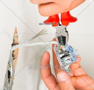 Close-up Of Electrician's Hand Installing Electrical Outlet On Wall Stock Photo