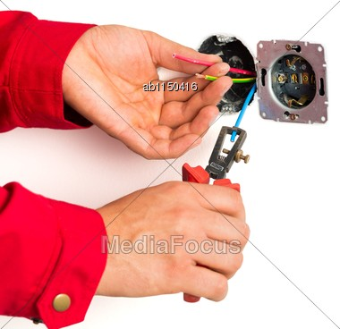 Close-up Of Electrician Working With Wire Stripping Pliers Stock Photo