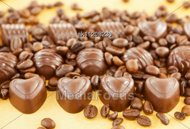 Close Up Of Heart Shaped Chocolate Candies And Coffee Beans Stock Photo