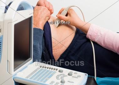 Close-up Of Internist Investigating Senior Patient's Internal Organs On Ultrasound Stock Photo