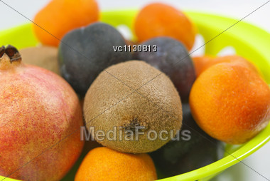 Close Up Of Mandarins, Kiwi, Pomegranate And Plums Fruits In The Green Plate Stock Photo