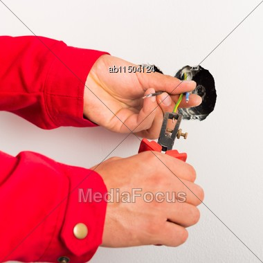 Close-up Of Electrician's Hands Stripping Wires Stock Photo