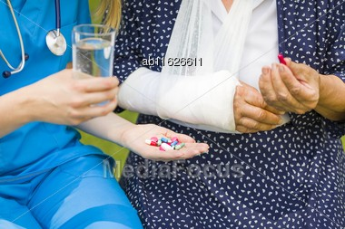 Closeup Of Caregiver Hands Giving Medication For Injured Elderly Patient With Gypsum Stock Photo