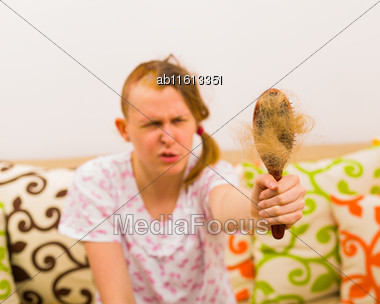 Closeup Of Full Hairbrush Held By Woman With Grimace Because Of Depression Stock Photo