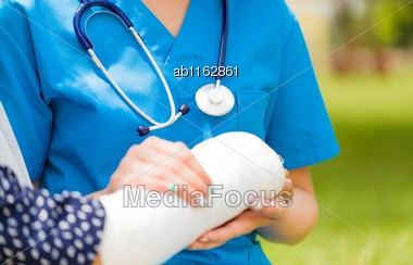 Closeup Of Holding Hands For Convalescence Of Old Woman's Broken Arm Bone With Bandage Stock Photo