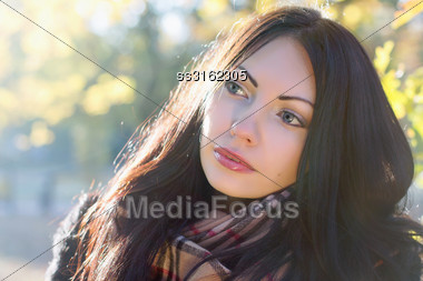 Closeup Portrait Of A Nice Young Brunette In Autumn Park Stock Photo