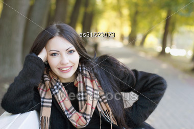 Closeup Portrait Of A Smiling Young Woman In Autumn Park Stock Photo