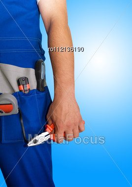 Closeup Of Repairman With Pliers On Blue Background Stock Photo